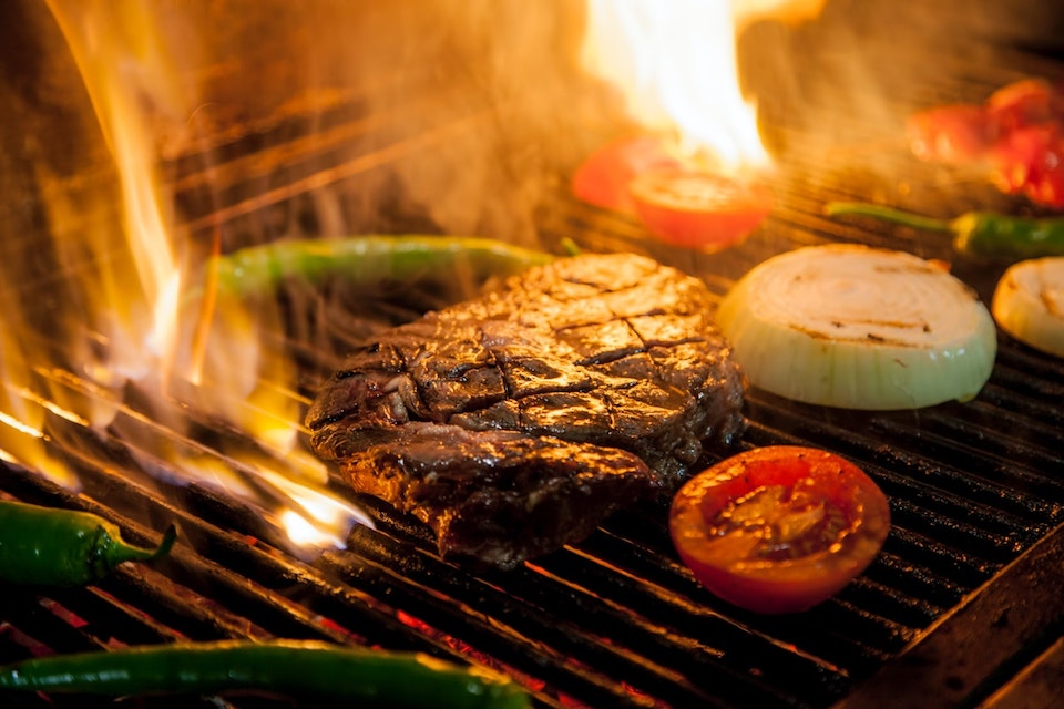 steak and vegetables on flaming grill